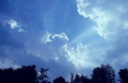 Perfect blue sky and dramatic clouds with the sun and it's rays shooting upward from behind the clouds