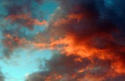 Brilliant and dramatic red colored clouds by the sunset in Arizona against a blue sky