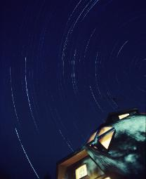 Star trails from a long exposure recording earth's rotation and how the stars paint streaks of light on film with a dome home in the foreground