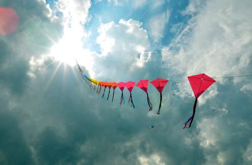 Photograph of one string of 70 multi-colored kites flying, trailing and disappearing into the sun.
