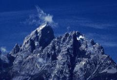 Photo of the Grand Teton peak with wispy clouds around the top against blue sky