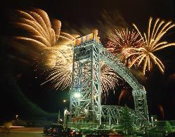Conrail lift bridge in Cleveland, Ohio's flats illuminated and with fireworks behind it