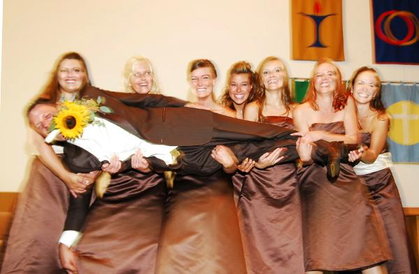 Groom with sunflower in his teeth being held up by six bridesmaids
