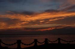 Photo of beautiful sunset over Lake Erie off the 9th Street Pier, Cleveland, Ohio with chain rail shadow in foreground.