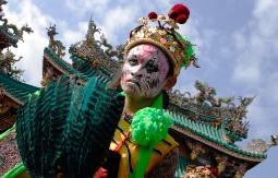 Magnificent photograph of a Taiwanese festival performer bejeweled and painted against the ornate dragon carvings of the temple roof.