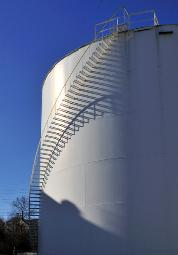 photograph of a massive holding tank with curved stairs leading up to the top of the tank with the sun casting great shadows on the tank