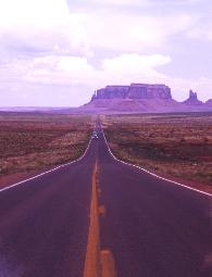 photograph of Monument Valley, Arizona - photo taken in the middle of the long stretch of highway with rock formations on the horizon