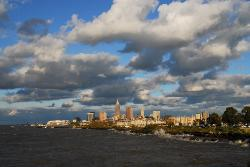Downtown Cleveland skyline on a sunny day with white clouds and rough lake waves from Lake Erie