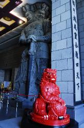 Red lion statue with huge guard statue at Chung Tai Chan Monastery in Taiwan