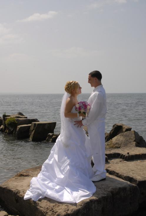 Bride and Groom at lakefront on the rocks