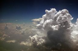 Tall beautiful cumulo nimbus clouds and a blue sky taken through a jet airliner window
